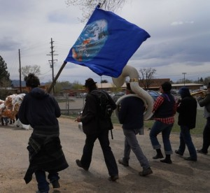 Brave New Burro (the brass band) and a windblown Earth Flag carrier during the Global Climate Convergence Community Parade in Taos, NM.