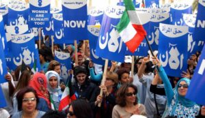 KUWAIT CITY, KUWAIT:  Kuwaiti women demonstrate in front of the parliament building in Kuwait City to demand their political rights, 07 March 2005. As a battle has raged in the Gulf emirate over political rights for its disenfranchised women, female activists and their liberal supporters staged the rally the morning the parliament was scheduled to discuss a government request to speed up the debate on a women's rights bill. The bill, approved by the cabinet last May and opposed by Islamic hardliners, calls for amending article one of the 1962 electoral law which limits voting and candidacy to male citizens whereas the constitution stipulates gender equality.  AFP PHOTO/YASSER AL-ZAYYAT  (Photo credit should read YASSER AL-ZAYYAT/AFP/Getty Images)